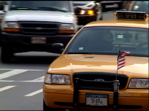 autumn 2001- small american flag attached to grill of yellow cab moving through traffic. - veicolo di terra per uso personale video stock e b–roll
