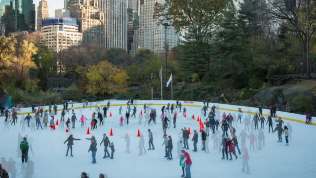 Autumn, afternoon time lapse of ice skaters on a crowded Wollman Rink in Central Park zooming out to reveal the New York City skyline
