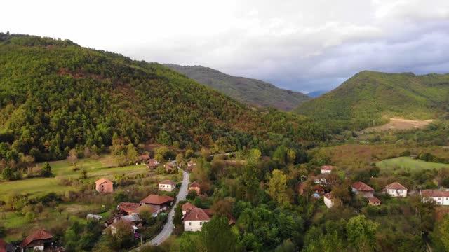 colori autunnali sopra il villaggio di montagna - video dall'alto, vista aerea di un villaggio di montagna incredibilmente bello nella serbia orientale - top capo di vestiario video stock e b–roll