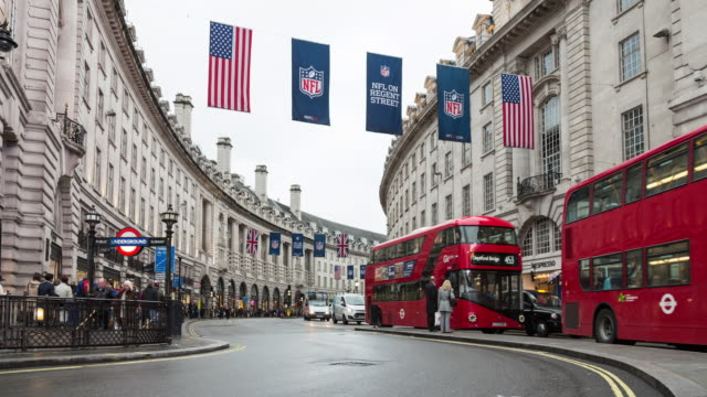 Autumn day time lapse of traffic along Regent St at Piccadilly Circus, featuring flags promoting the NFL exhibition games being played in London
