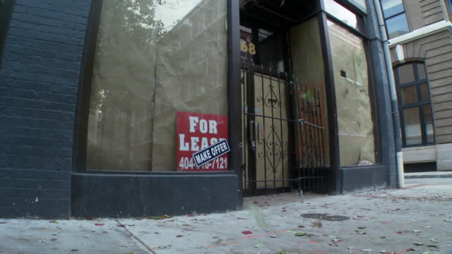 ms, tu, autumn leaves falling in front of shop for lease, atlanta, georgia, usa - 打ち捨てられた点の映像素材/bロール