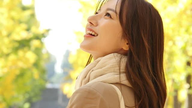 autumn mood - young woman enjoying autumn in park - バッグ点の映像素材/bロール