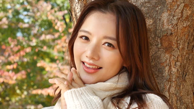 autumn mood - young woman leaning against tree and looking at camera with smile - 横顔点の映像素材/bロール