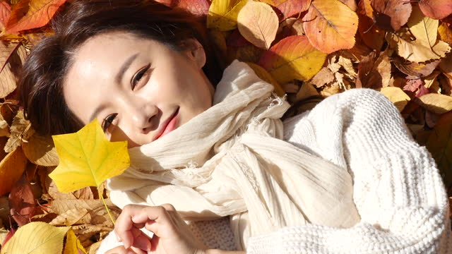 vídeos de stock, filmes e b-roll de autumn mood - young woman lying in park and enjoying autumn with holding fallen leaves - suéter