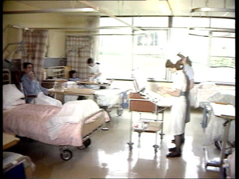 Autumn statement Hospital trolley MS Patients in beds as nurses at drugs PAN CMS Nurse pushing drugs trolley along