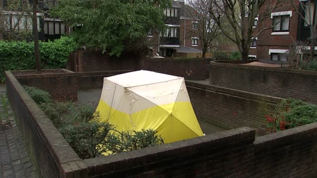 police cuts in london / teenager stabbed to death in holloway london holloway ext block of flats pan white and yellow forensic tent police car and... - vaso stock videos and b-roll footage