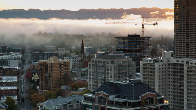 Autumn sunrise time lapse of the First Hill neighborhood in Seattle with fog rolling across the cityscape and featuring a prominent construction crane
