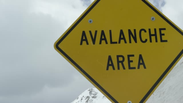 """avalanche area"" caution road sign in the rocky mountains of colorado under an overcast sky in winter - road warning sign stock videos & royalty-free footage"