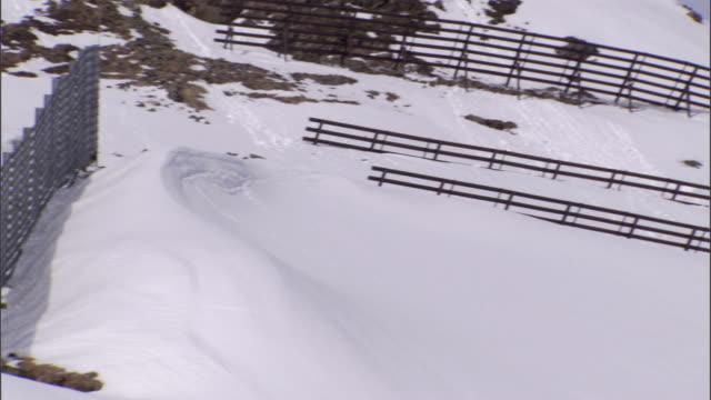 ws pan avalanche fences sticking out of snow on  mountain ridge/ davos, graubünden, switzerland - fence stock videos & royalty-free footage