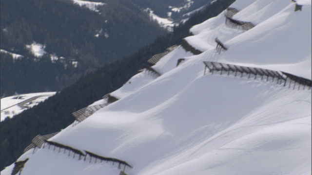 vidéos et rushes de ms tu avalanche fences sticking out of the snow on mountain ridge / davos, graubünden, switzerland - limite