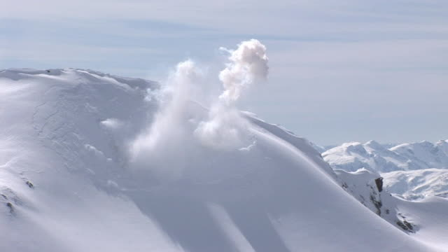 WS Avalanche of snow flowing down over rock mountain side / Revelstoke, British Columbia, Canada