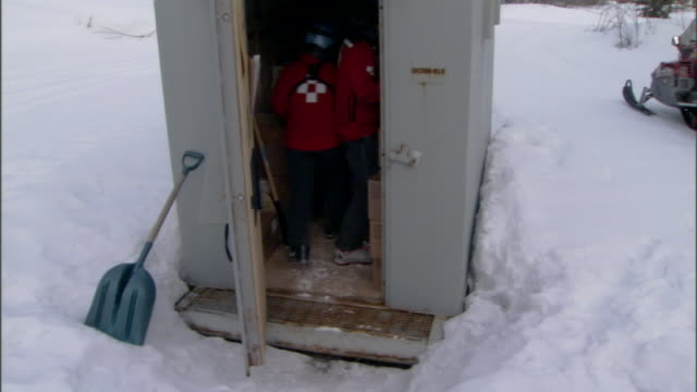 avalanche simulation crew members remove bags of explosives from a shed. - shed stock videos & royalty-free footage