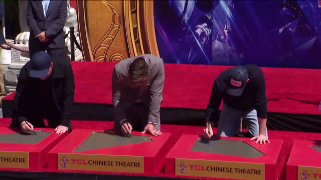 'avengers' cast gets their hands and feet cemented at tcl chinese theater in hollywood california - tcl chinese theater stock-videos und b-roll-filmmaterial