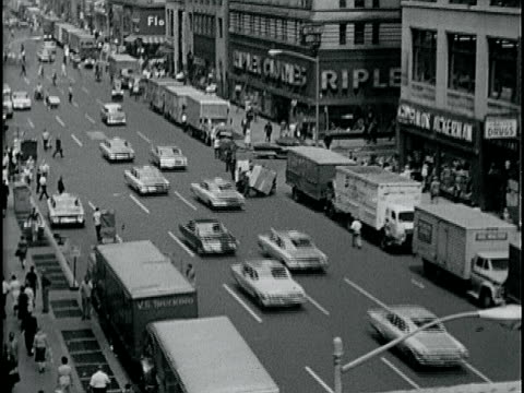 avenue w/ taxi cabs traffic moving south trucks parked both sides of street young adult males pulling four racks of covered clothing black male... - anno 1963 video stock e b–roll