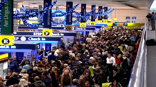 airport delays and cancellations due to fog continue; tx int high angle view of travellers queuing in crowded airport terminal - crowded airport stock videos & royalty-free footage