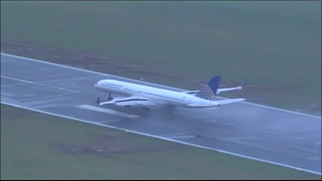 bristol airport reopens after safety concerns; england: bristol: bristol airport: ext / rain high angle shot of plane coming into land on wet tarmac... - landing touching down stock videos & royalty-free footage
