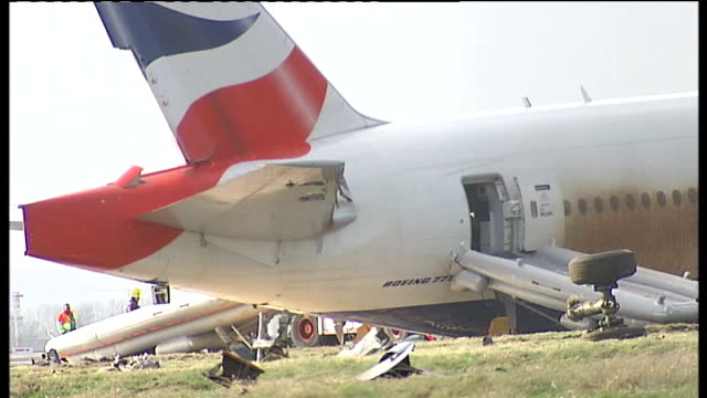 British Airways plane crashes leaving noone hurt Investigators examining wreckage of crashed Boeing 777 plane / Tail end of plane with rippedoff...