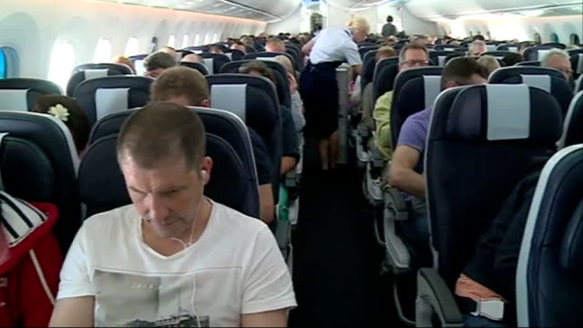 dreamliner 787 first commercial uk flight boeing 787 dreamliner passenger putting bag into overhead luggage storage area passenger operating window... - air stewardess stock videos & royalty-free footage