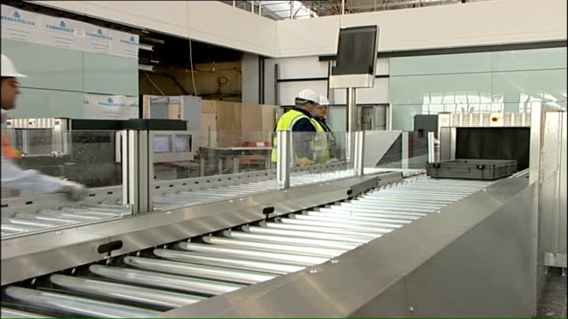 heathrow airport terminal five to open in march 2008; int new check-in area and departure information boards trays along rollers to x-ray machine... - headwear stock videos & royalty-free footage