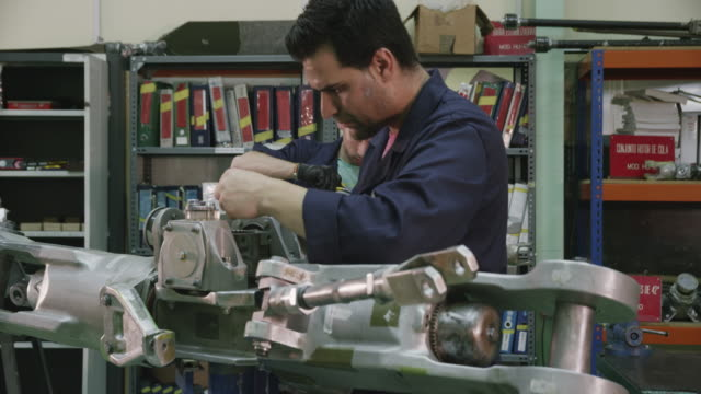 DS MS aviation mechanic trainees at work on aircraft components  in the workshop of a training facility, RED R3D 4k