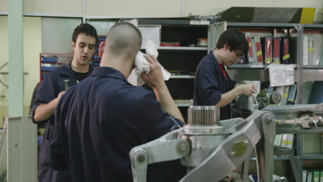 DS MS aviation mechanic trainees at work on aircraft components  in the workshop of a training facility, one trainee wiping sweat off his face, RED R3D 4k