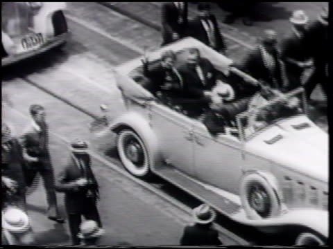 Aviation pioneer pilot Amelia Earhart riding waving in backseat of open convertible car MS Amelia standing in back seat of car waving while holding...