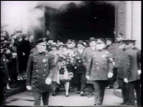 Aviation pioneer Ruth Elder being escorted by police to car CU Ruth in cloche hat smiling talking