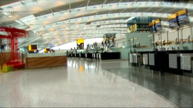 Queen opens Heathrow Airport Terminal 5 SPEEDED UP TRACK FORWARD past workers wearing hardhats and through concourse of empty checkin area Reporter...
