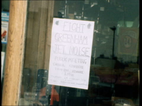 residents protest against use of greenham common airbase; england: berkshire: newbury: tobacconist shop window zoom into notice of protest in window;... - newbury inghilterra video stock e b–roll