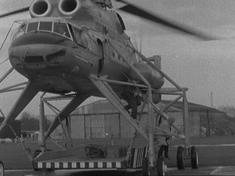 russian mil mi-10 helicopter lands at gatwick; england: lap: : ext g/a cccp-04102 mil mi-10 heavy lift helicopter flies in behind hangar: ^g/a... - propeller stock videos & royalty-free footage