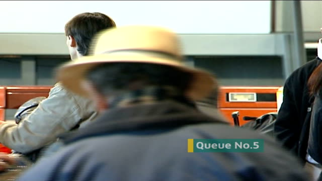 third day of fog delays at heathrow airport; people milling at check-in desk dissolve to... - 3日目点の映像素材/bロール