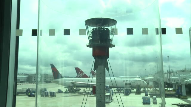 view from air traffic control tower england london heathrow int gv's delta and virgin planes parked at gate / baggage unloaded with lift / baggage... - air traffic control点の映像素材/bロール