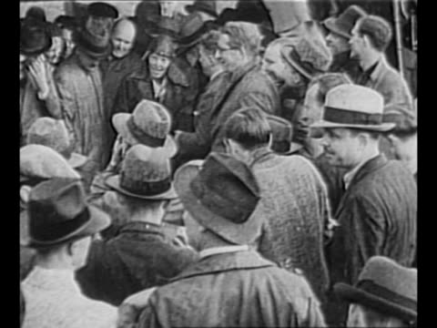 Aviator Amelia Earhart surrounded by crowd after landing in Ireland / Earhart barely seen walks with crowd on airfield / Earhart talks to men at...