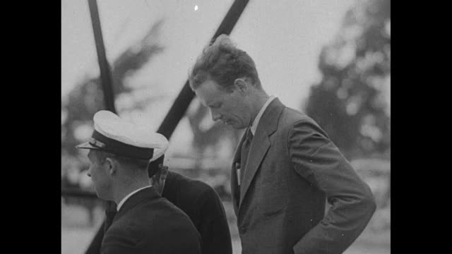 Aviator Charles Lindbergh stands with men / Lindbergh walks on top of 'American Clipper' Sikorsky S40 seaplane prior to takeoff / crowd stands on...