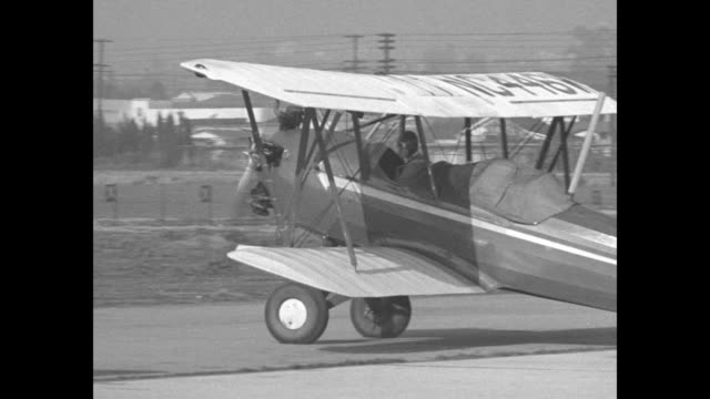 aviator laura ingalls standing next to plane talking to camera about flying on instruments / ingalls taxiing in biplane / ingalls taking off in... - blindness stock videos & royalty-free footage