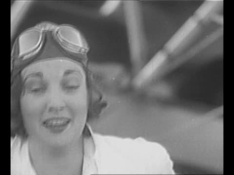 aviator ruth elder stands in front of plane wearing flight jumpsuit helmet and goggles sit on her head / elder speaks smiles winks / cu elder at the... - jumpsuit stock videos & royalty-free footage