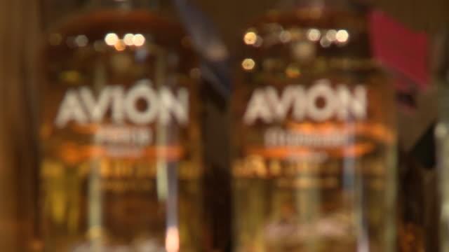stockvideo's en b-roll-footage met avion reposado tequila, across to avion silver and patron, tequila on shelf, liquor store window with avion advertisement - avion
