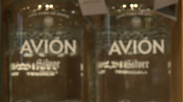 avion silver tequila, various boxes of avion silver tequila and bottles on display on store shelf, other brands of avion on display - avion stock-videos und b-roll-filmmaterial