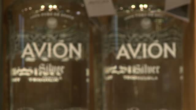 stockvideo's en b-roll-footage met avion silver tequila, various boxes of avion silver tequila and bottles on display on store shelf, other brands of avion on display - avion