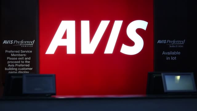 vídeos de stock e filmes b-roll de avis budget group inc. signage is displayed behind an avis rental car counter at indianapolis international airport in indianapolis, indiana, u.s.,... - aluguer de automóveis