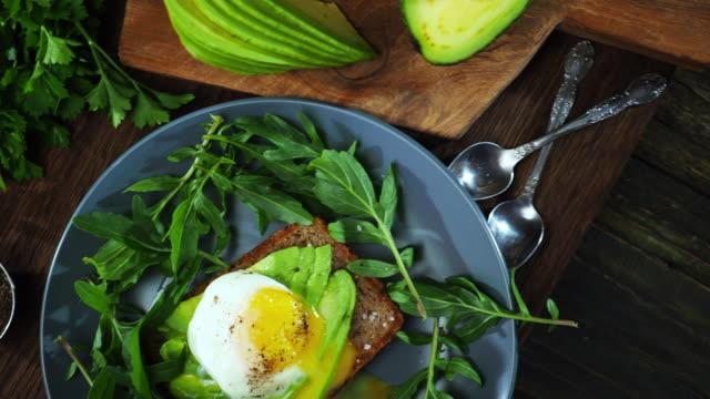 vídeos de stock e filmes b-roll de avocado and egg sandwich - sanduíche