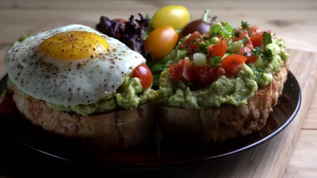 avocado toast topped with diced tomatoes chopped green onion drizzled with olive oil and fried egg - healthy plate stock videos & royalty-free footage
