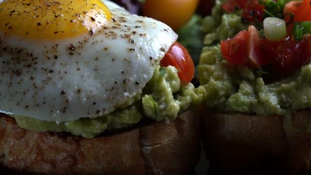 stockvideo's en b-roll-footage met avocado toast gegarneerd met blokjes tomaten, gehakte groene ui besprenkeld met olijfolie en gebakken ei - gebakken ei