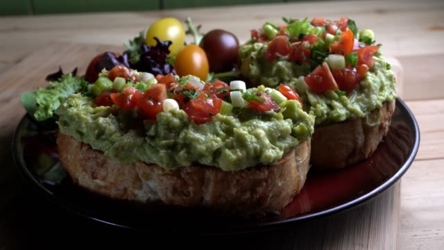 avocado toast topped with diced tomatoes chopped green onion drizzled with oliv oil - sandwich stock videos & royalty-free footage