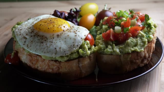 avocado toast topped with diced tomatoes chopped green onion drizzled with olive oil and fried egg - chopped food stock videos and b-roll footage