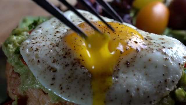 Avocado Toast Topped With Diced Tomatoes Green Onion And Fried Egg With Fork Piercing The Yolk