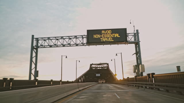 """avoid non-essential travel"" advisory on a road sign on general pulaski skyway bridge flashing because of covid-19 coronavirus pandemic in new jersey. driver point of view. - road sign stock videos & royalty-free footage"