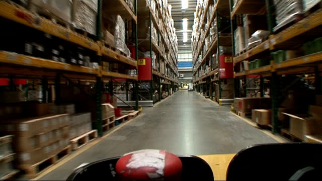 avoids triple dip recession; england: east midlands: northampton: travis perkins distribution centre: int tracking shot from forklift truck driving... - northampton england stock videos & royalty-free footage