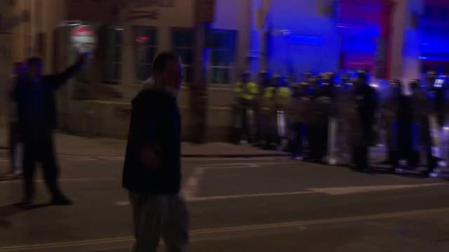 avon and somerset police under scrutiny following bristol riots; england: bristol: ext / night riot police in line as protester hits police shields... - scrutiny stock videos & royalty-free footage
