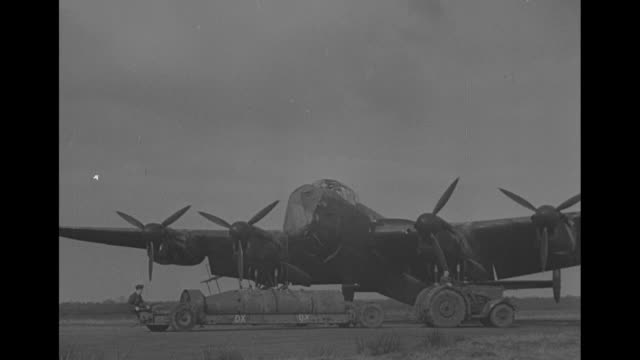 ms avro lancaster plane with tractor pulling blockbuster bomb on trailer in front of it / vs soldier riding on and bracing bomb as tractor pulls it /... - lancaster bomber stock videos & royalty-free footage